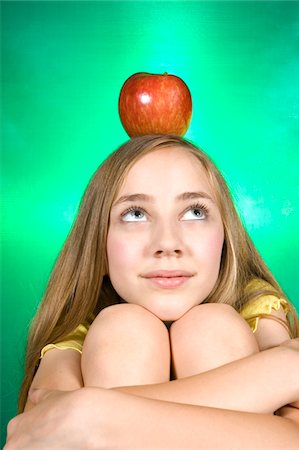 preteen  smile  one  alone - Young girl with an apple on her head Stock Photo - Premium Royalty-Free, Code: 6106-05494095