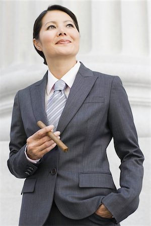 Asian Businesswoman with Cigar Stock Photo - Premium Royalty-Free, Code: 6106-05496016