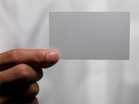 Woman holding blank business card Stock Photo - Premium Royalty-Free, Code: 6106-05496135