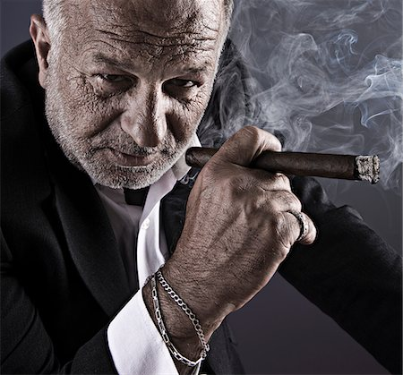 Mature businessman smoking cigar with hairy hands Stock Photo - Premium Royalty-Free, Code: 6106-05496231