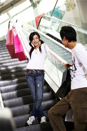 Man and woman with shopping bags on escalator Stock Photo - Premium Royalty-Free, Code: 6106-05496776