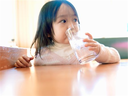 Girl who drinks water at a restaurant Stock Photo - Premium Royalty-Free, Code: 6106-05499995