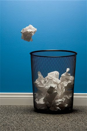 Crumpled paper about to fall into waste basket Stock Photo - Premium Royalty-Free, Code: 6106-05402647