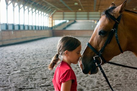 preteen kissing - Girl nose to nose with horse in riding arena. Stock Photo - Premium Royalty-Free, Code: 6106-05402790