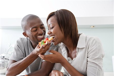 Couple sharing pizza in their kitchen Stock Photo - Premium Royalty-Free, Code: 6106-05402914