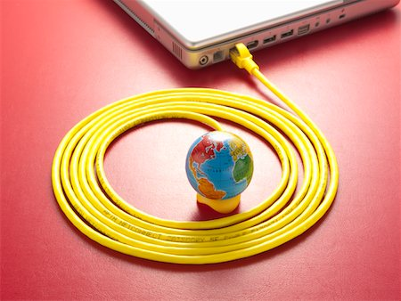 Yellow LAN cable and a globe. Stock Photo - Premium Royalty-Free, Code: 6106-05403900