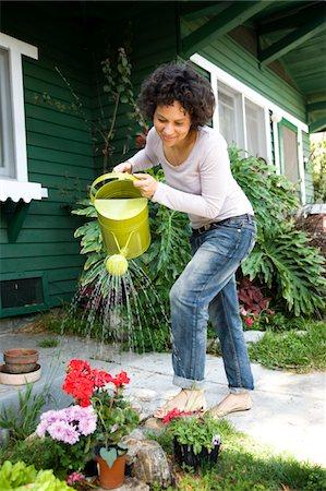 Woman watering flowers Stock Photo - Premium Royalty-Free, Code: 6106-05404435