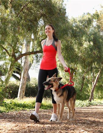 Girl walking dog on tree lined path Stock Photo - Premium Royalty-Free, Code: 6106-05405436