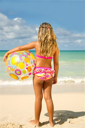 Girl with beach ball looking out at ocean. Stock Photo - Premium Royalty-Free, Code: 6106-05405915