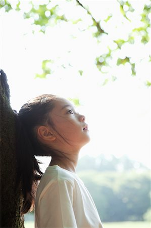 Young girl looking up outdoors Stock Photo - Premium Royalty-Free, Code: 6106-05406445