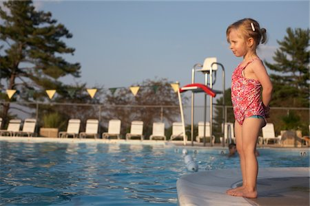 Young girl standing at edge of pool Stock Photo - Premium Royalty-Free, Code: 6106-05406942