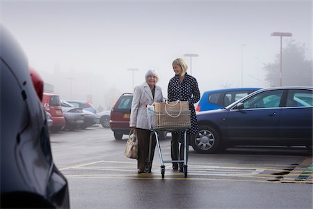 person walking on parking lot - senior supermarket shopper with female volunteer Stock Photo - Premium Royalty-Free, Code: 6106-05409790