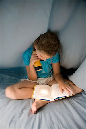 Girl reading under the covers with flashlight Stock Photo - Premium Royalty-Free, Code: 6106-05410276