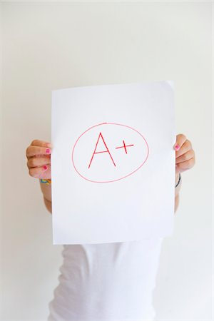 Girl showing off A+ grade on paper Stock Photo - Premium Royalty-Free, Code: 6106-05410283