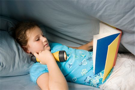 Girl reading under the covers with flashlight Stock Photo - Premium Royalty-Free, Code: 6106-05410287