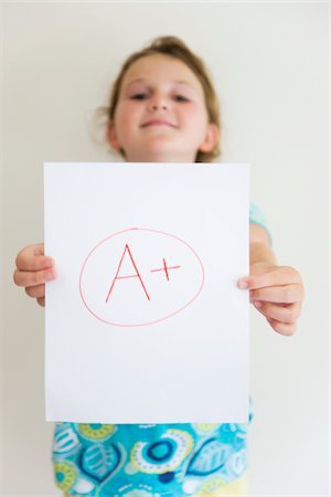 Girl showing off A+ grade on paper Stock Photo - Premium Royalty-Free, Code: 6106-05410289