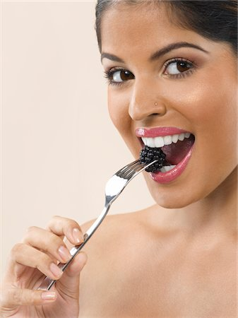 Woman Eating Blackberry Stock Photo - Premium Royalty-Free, Code: 6106-05412042