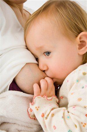 Woman's breast feeding her daughter. Stock Photo - Premium Royalty-Free, Code: 6106-05413120
