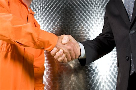 Businessman and manual worker shaking hands Stock Photo - Premium Royalty-Free, Code: 6106-05413294