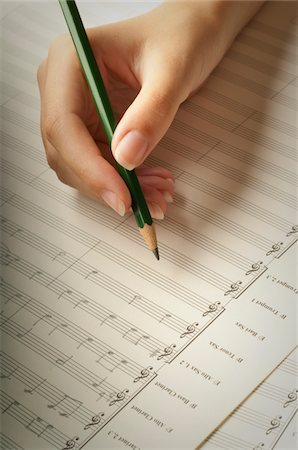 Young woman's hand writing music score Stock Photo - Premium Royalty-Free, Code: 6106-05416841