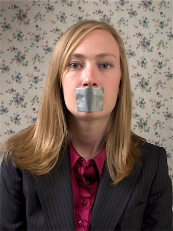 Businesswoman with duct tape over mouth Stock Photo - Premium Royalty-Free, Code: 6106-05423640