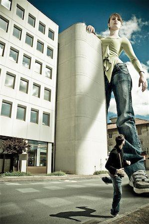 dominant woman - Beautiful giant girl pursuit man in urban scenery Stock Photo - Premium Royalty-Free, Code: 6106-05427082