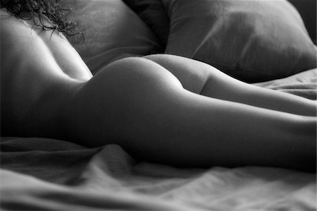 Naked young woman lying down on her bed Stock Photo - Premium Royalty-Free, Code: 6106-05427012