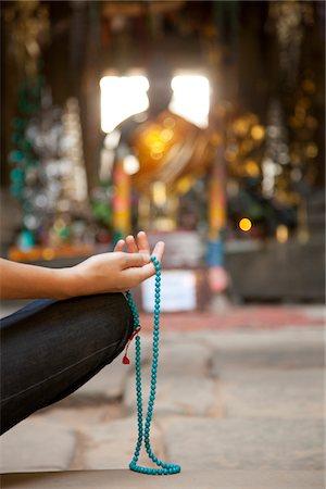 Person meditating with mala, Buddhist prayer beads Stock Photo - Premium Royalty-Free, Code: 6106-05428553