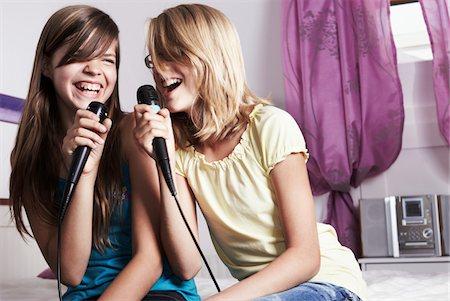 preteen girl - Two girls doing karaoke in bedsit Stock Photo - Premium Royalty-Free, Code: 6106-05431626