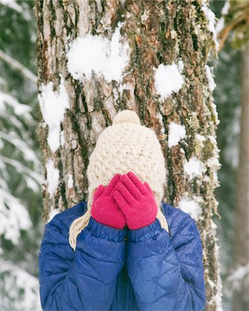A Woman hiding her face in her hands in the snow Stock Photo - Premium Royalty-Free, Code: 6106-05431904