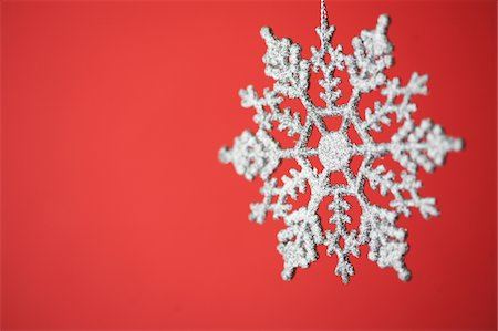 snowflakes  holiday - Snowflake Christmas ornament on red background Stock Photo - Premium Royalty-Free, Code: 6106-05432429
