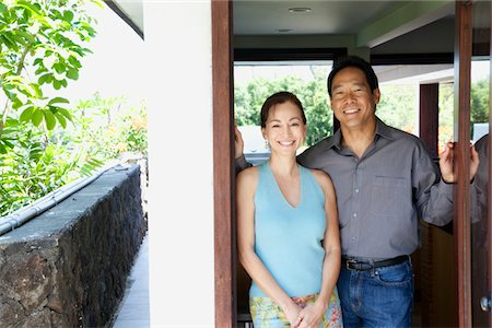 Happy, mature couple standing in doorway to home Stock Photo - Premium Royalty-Free, Code: 6106-05437883