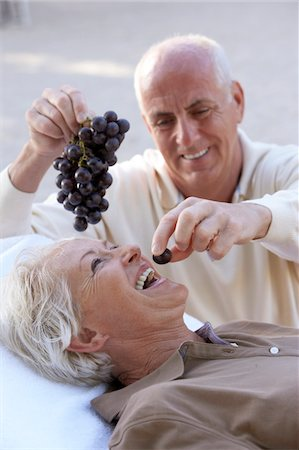 Mature man feeding grapes to woman, laughing Stock Photo - Premium Royalty-Free, Code: 6106-05542964