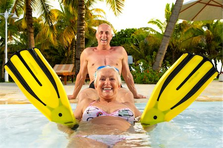 seniors woman in swimsuit - Mature couple playing in pool, laughing, portrait Stock Photo - Premium Royalty-Free, Code: 6106-05542982