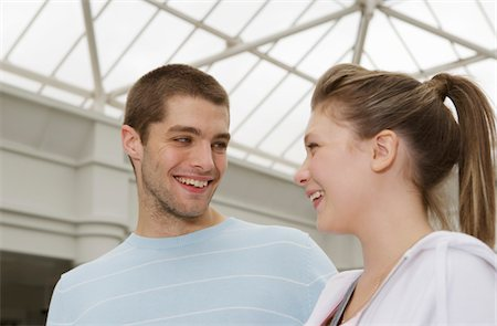 Teenage couple (15-17) smiling at each other, close-up Stock Photo - Premium Royalty-Free, Code: 6106-05543550