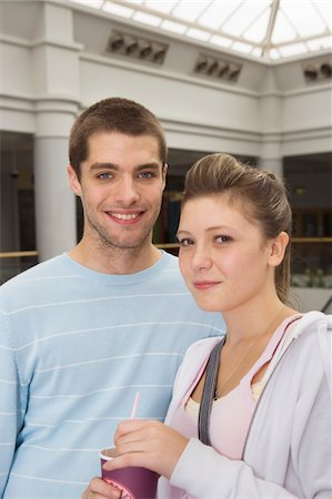 Teenage couple (15-17) in shopping centre, smiling, portrait, close-up Stock Photo - Premium Royalty-Free, Code: 6106-05543551