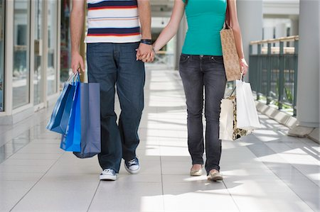 Teenage couple (15-17) walking hand in hand carrying bags, low section Stock Photo - Premium Royalty-Free, Code: 6106-05543557