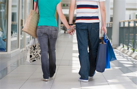 Teenage couple (15-17) in shopping centre, low section, rear view Stock Photo - Premium Royalty-Free, Code: 6106-05543558