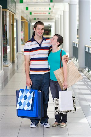 Teenage couple (15-17) in shopping centre with bags, portrait of boy Stock Photo - Premium Royalty-Free, Code: 6106-05543559