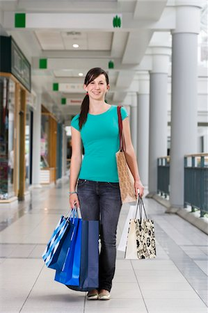 Teenage girl (15-17) in shopping centre holding bags, portrait Stock Photo - Premium Royalty-Free, Code: 6106-05543561
