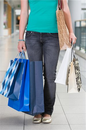 Teenage girl (15-17) in shopping centre with bags, low section Stock Photo - Premium Royalty-Free, Code: 6106-05543562