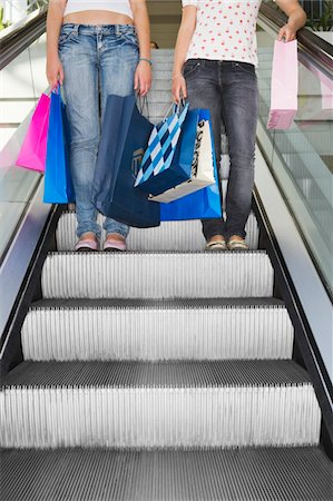 Two teenage girls (15-17) on escalator with bags, low section Stock Photo - Premium Royalty-Free, Code: 6106-05543566