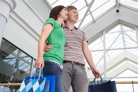 Teenage couple (15-17) in shopping centre with bags, low angle view Stock Photo - Premium Royalty-Free, Code: 6106-05543537