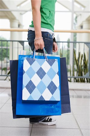 Teenage girl (15-17) in shopping centre with bags, low section Stock Photo - Premium Royalty-Free, Code: 6106-05543534