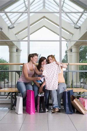 Teenage girls (15-17) in shopping centre looking at clothes purchase Stock Photo - Premium Royalty-Free, Code: 6106-05543539