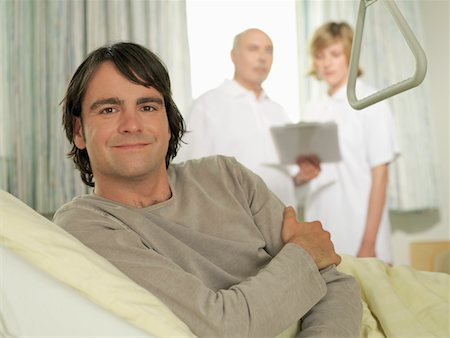 Male patient lying in bed, smiling, portrait, doctors in background Stock Photo - Premium Royalty-Free, Code: 6106-05543724