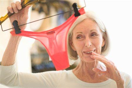 Senior woman holding thong panties in retail store Stock Photo - Premium Royalty-Free, Code: 6106-05547582