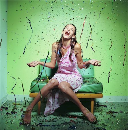 Young woman in polka dot dress being showered with confetti Stock Photo - Premium Royalty-Free, Code: 6106-05561205