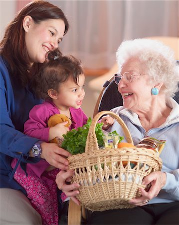 Mother and daughter (18-21 months) giving food basket to senior woman Stock Photo - Premium Royalty-Free, Code: 6106-05562860