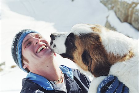 Saint Bernard licking young man's face Stock Photo - Premium Royalty-Free, Code: 6106-05564161